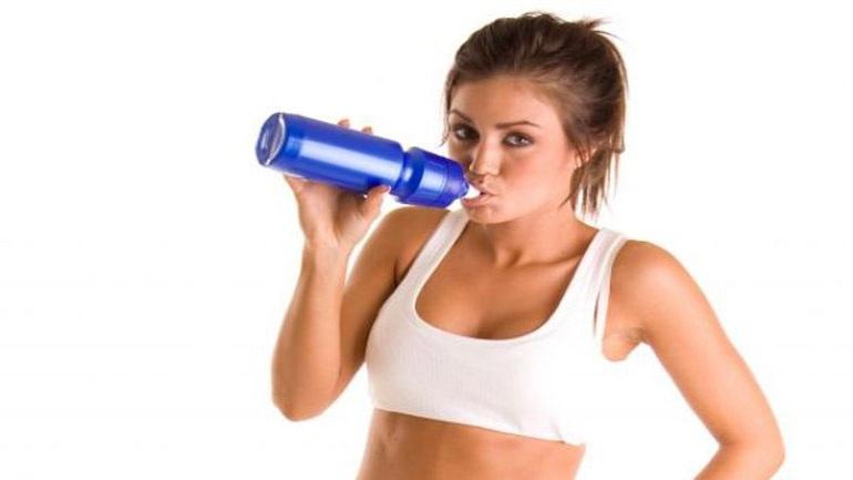 Κοπέλα πίνει νερό μετά το γυμναστήριο